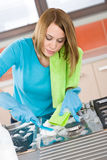 Young woman cleaning stove in kitchen Stock Photo