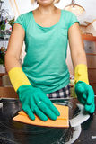 Young woman cleaning stove in kitchen Stock Image