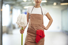 Young woman with cleaning supplies in building Stock Photo