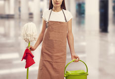 Young woman with cleaning supplies in building Stock Image