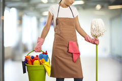 Young woman with cleaning supplies in building