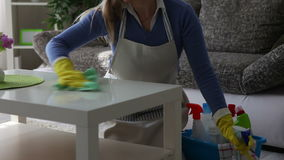 Young woman cleaning the table close-up