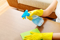 Young woman cleaning  table in yellow gloves Royalty Free Stock Image