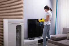 Young Woman Cleaning Television stock image