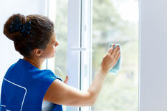 Young Woman cleaning window glass. Cleaning Company Worker Royalty Free Stock Images