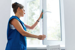 Young Woman cleaning window glass. Cleaning Company Worker Stock Images