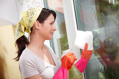 Young woman cleaning a window Royalty Free Stock Image