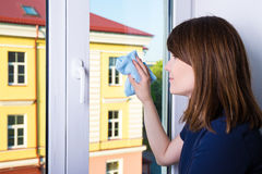 Young woman cleaning window with rag at home. Young woman cleaning window with special rag at home Stock Images
