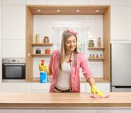 Young woman cleaning a wooden counter top in a kitchen stock photography