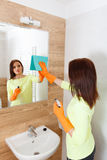 The young woman cleans a bathroom. Stock Image