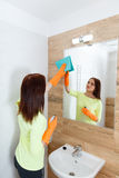 The young woman cleans a bathroom. Royalty Free Stock Photography