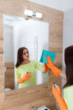 The young woman cleans a bathroom. Royalty Free Stock Photos