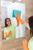 The young woman cleans a bathroom. Royalty Free Stock Images