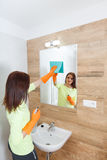 The young woman cleans a bathroom. Stock Photography