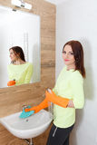 The young woman cleans a bathroom. Royalty Free Stock Image