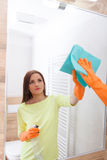 The young woman cleans a bathroom. Pretty young woman with housework. Girl cleans a bathroom, wash basin and mirror. Use detergents royalty free stock photography