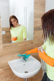 The young woman cleans a bathroom. Pretty young woman with housework. Girl cleans a bathroom, wash basin and mirror. Use detergents stock image