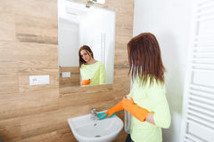 The young woman cleans a bathroom. Pretty young woman with housework. Girl cleans a bathroom, wash basin and mirror. Use detergents royalty free stock photo