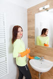 The young woman cleans a bathroom. Pretty young woman with housework. Girl cleans a bathroom, wash basin and mirror. Use detergents royalty free stock images