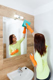 The young woman cleans a bathroom. Pretty young woman with housework. Girl cleans a bathroom, wash basin and mirror. Use detergents stock photography