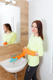 The young woman cleans a bathroom. Pretty young woman with housework. Girl cleans a bathroom, wash basin and mirror. Use detergents royalty free stock photos