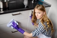 A young woman cleans the kitchen cabinets Royalty Free Stock Photos