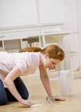 Young woman cleans spill Royalty Free Stock Image