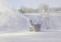 Young woman clearing drive with snowblower stock photos