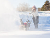Young woman clearing drive with snowblower Royalty Free Stock Image