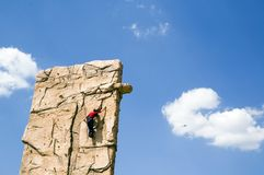 Young woman climb wall. A young woman climb a climbing wall. It is secured by rope, which leads by certain safeguarding points, against a crash. The climbing stock images