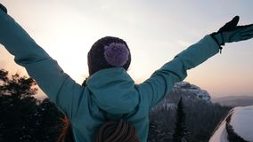 A young woman climber stands on top of a mountain and looks at the sunset. stock video footage