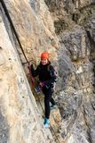 Young woman climber on a Via Ferret in the Dolomites. Young female climber wearing a red helmet on a Via Ferrata in the South Tyrol Royalty Free Stock Photography
