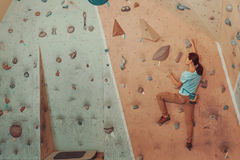 Young woman climbing artificial boulder in gym Royalty Free Stock Photography