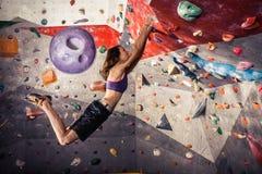Young woman climbing artificial boulder indoors Stock Image