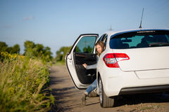 Young woman climbing into a car Stock Photography