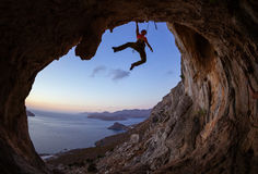 Young woman climbing in cave at sunset Royalty Free Stock Photography