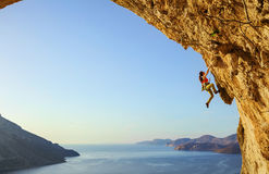 Young woman climbing challenging route in cave at sunset. Kalymnos island, Greece royalty free stock photos