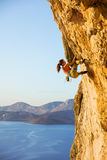 Young woman climbing challenging route. Before sunset royalty free stock photography
