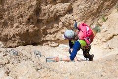 Young woman climbing desert canyon cliff. Stock Photos