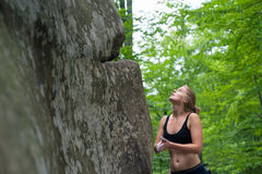 Young woman with climbing equipment in front of a stone Stock Photos