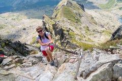 Young woman climbing high mountains Stock Photos