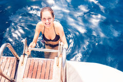 Young Woman Climbing Out Of The Sea stock photo