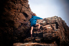 Young woman climbing a rock Royalty Free Stock Photos