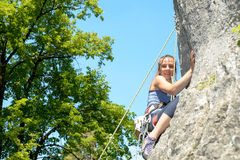 Young woman climbing a rock wall Stock Photo