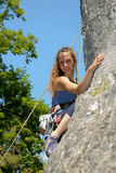 Young woman climbing a rock wall Royalty Free Stock Photography