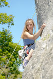 Young woman climbing a rock wall Royalty Free Stock Image