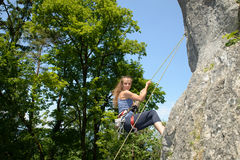 Young woman climbing a rock wall Stock Images