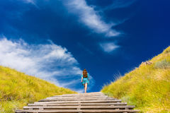 Young woman climbing stairs outdoors in an idyllic travel destin. Full length rear view of a young woman wearing a blue dress while climbing wooden stairs Royalty Free Stock Photography