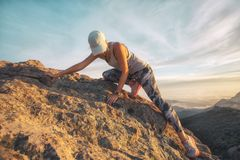 A young woman climbing a steep rocky mountain high above the sea level at Sandstone Peak, Malibu, California. A young woman climbing a steep rock mountain Stock Images