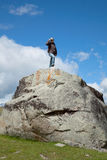 A young woman climbs on the cliff top Stock Photography